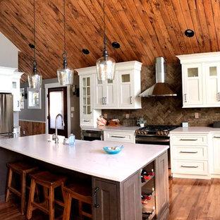 Idées déco pour une cuisine ouverte bord de mer en U de taille moyenne avec un évier de ferme, un placard avec porte à panneau encastré, des portes de placard blanches, un plan de travail en quartz, une crédence marron, une crédence en brique, un électroménager en acier inoxydable, un sol en bois foncé, un îlot central, un sol marron et un plan de travail blanc.