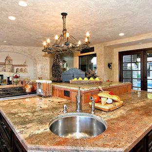 Große Mediterrane Wohnküche in L-Form mit Waschbecken, Schrankfronten mit vertiefter Füllung, schwarzen Schränken, Granit-Arbeitsplatte, Küchenrückwand in Rot, Rückwand aus Terrakottafliesen, Küchengeräten aus Edelstahl, Porzellan-Bodenfliesen und Kücheninsel in San Diego