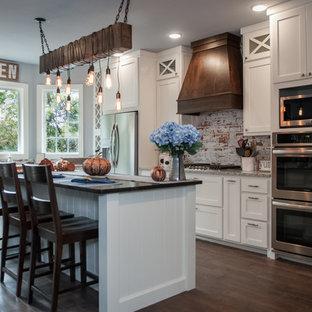 他の地域の大きいトランジショナルスタイルのおしゃれなキッチン (エプロンフロントシンク、シェーカースタイル扉のキャビネット、白いキャビネット、御影石カウンター、マルチカラーのキッチンパネル、レンガのキッチンパネル、シルバーの調理設備の、茶色い床、グレーのキッチンカウンター) の写真