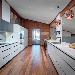 アデレードの大きいコンテンポラリースタイルのおしゃれなキッチン (ダブルシンク、白いキャビネット、ラミネートカウンター、シルバーの調理設備の、無垢フローリング、ガラス板のキッチンパネル、フラットパネル扉のキャビネット) の写真