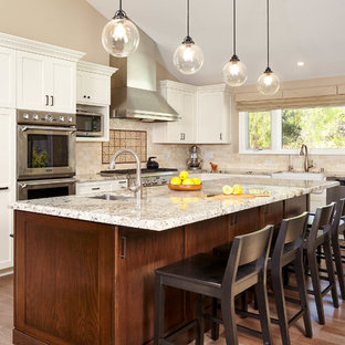 Photo of a large traditional l-shaped kitchen in San Francisco with a belfast sink, shaker cabinets, white cabinets, granite worktops, beige splashback, ceramic splashback, stainless steel appliances, medium hardwood flooring, an island and brown floors.