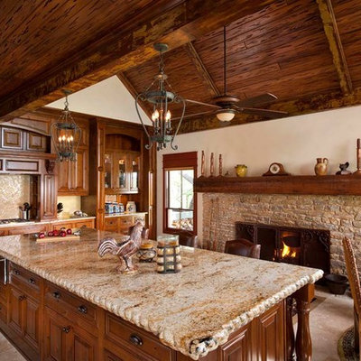Eat-in kitchen - rustic eat-in kitchen idea in Dallas with raised-panel cabinets, medium tone wood cabinets and beige backsplash