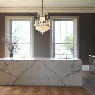 Offene, Große Moderne Küche mit flächenbündigen Schrankfronten, braunen Schränken, Marmor-Arbeitsplatte, Kücheninsel, Unterbauwaschbecken und braunem Holzboden in London