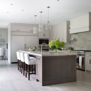 Transitional kitchen ideas - Example of a transitional light wood floor kitchen design in New York with an undermount sink, shaker cabinets, beige cabinets, white backsplash, stone slab backsplash, paneled appliances and an island