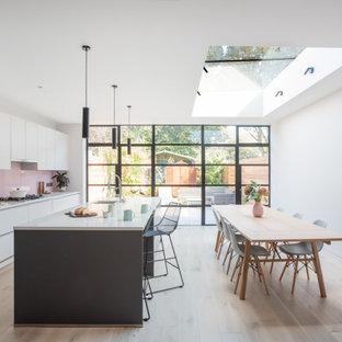 Ispirazione per una cucina contemporanea di medie dimensioni con lavello da incasso, ante lisce, ante grigie, top in quarzite, paraspruzzi rosa, paraspruzzi con lastra di vetro, parquet chiaro, isola e top bianco