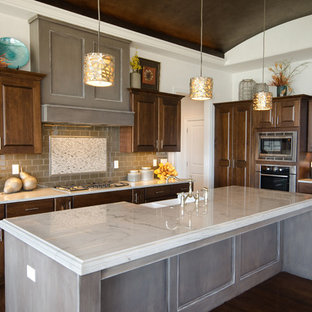 Inspiration for a mid-sized contemporary l-shaped dark wood floor open concept kitchen remodel in Wichita with a farmhouse sink, recessed-panel cabinets, dark wood cabinets, granite countertops, gray backsplash, subway tile backsplash, stainless steel appliances and an island