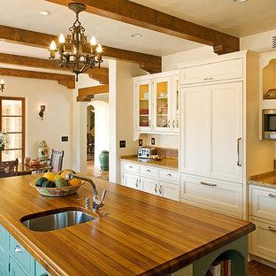 Diseño de cocina comedor en U, campestre, grande, con armarios con paneles empotrados, puertas de armario blancas, encimera de madera, salpicadero multicolor, salpicadero de azulejos de terracota, electrodomésticos con paneles, suelo de baldosas de porcelana y una isla
