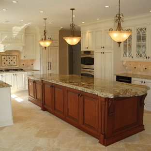 Large elegant u-shaped travertine floor and brown floor enclosed kitchen photo in Philadelphia with raised-panel cabinets, white cabinets, granite countertops, beige backsplash, travertine backsplash, paneled appliances, an island and brown countertops