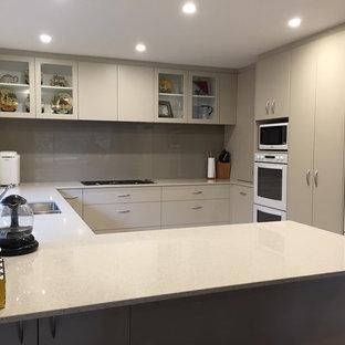 クライストチャーチの大きいコンテンポラリースタイルのおしゃれなキッチン (アンダーカウンターシンク、フラットパネル扉のキャビネット、ベージュのキャビネット、クオーツストーンカウンター、茶色いキッチンパネル、ガラス板のキッチンパネル、白い調理設備、磁器タイルの床) の写真