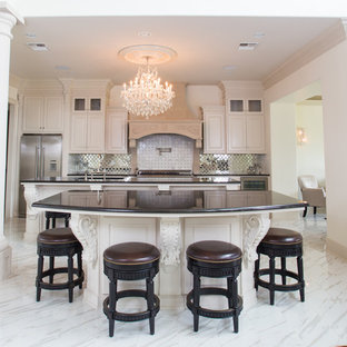 Design ideas for an expansive victorian single-wall open plan kitchen in New Orleans with a double-bowl sink, white cabinets, granite benchtops, metallic splashback, glass tile splashback, stainless steel appliances, ceramic floors and multiple islands.