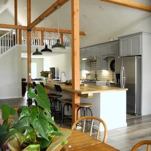 デンバーのインダストリアルスタイルのおしゃれなキッチン (エプロンフロントシンク、シェーカースタイル扉のキャビネット、グレーのキャビネット、木材カウンター、マルチカラーのキッチンパネル、シルバーの調理設備、クッションフロア) の写真