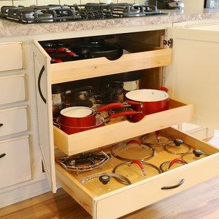 Immagine di una cucina chic di medie dimensioni con ante con bugna sagomata, ante con finitura invecchiata, top in laminato, paraspruzzi bianco, paraspruzzi con piastrelle in ceramica, elettrodomestici neri, pavimento in linoleum e isola