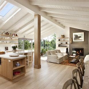 Mid-sized trendy light wood floor open concept kitchen photo in Santa Barbara with flat-panel cabinets, medium tone wood cabinets, quartz countertops, white backsplash and paneled appliances