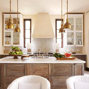 Foto på ett medelhavsstil kök och matrum, med en undermonterad diskho, luckor med glaspanel, vita skåp, flerfärgad stänkskydd, rostfria vitvaror och en köksö
