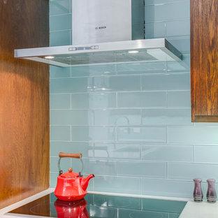 ダラスの中サイズのミッドセンチュリースタイルのおしゃれなキッチン (アンダーカウンターシンク、フラットパネル扉のキャビネット、中間色木目調キャビネット、クオーツストーンカウンター、青いキッチンパネル、ガラスタイルのキッチンパネル、シルバーの調理設備の、白いキッチンカウンター) の写真