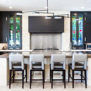 Ejemplo de cocina en L, tradicional renovada, con fregadero bajoencimera, armarios estilo shaker, puertas de armario negras, salpicadero metalizado, electrodomésticos de acero inoxidable, una isla, suelo beige y encimeras beige
