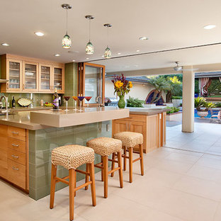 Design ideas for a large tropical u-shaped eat-in kitchen in Santa Barbara with an undermount sink, shaker cabinets, light wood cabinets, quartz benchtops, green splashback, glass tile splashback, stainless steel appliances, porcelain floors, with island and beige floor.