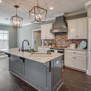 ニューオリンズの中くらいのおしゃれなキッチン (アンダーカウンターシンク、レイズドパネル扉のキャビネット、白いキャビネット、御影石カウンター、マルチカラーのキッチンパネル、レンガのキッチンパネル、シルバーの調理設備、クッションフロア、茶色い床、白いキッチンカウンター) の写真