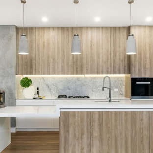 Photo of a contemporary kitchen in Melbourne with an undermount sink, flat-panel cabinets, light wood cabinets, grey splashback, marble splashback, black appliances, light hardwood floors, with island, beige floor and white benchtop.