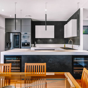 Inspiration for a contemporary u-shaped kitchen in Sunshine Coast with a drop-in sink, black appliances, medium hardwood floors, white benchtop, white cabinets, white splashback, porcelain splashback and with island.