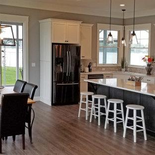Idéer för ett stort klassiskt vit l-kök, med en nedsänkt diskho, släta luckor, vita skåp, bänkskiva i kvarts, beige stänkskydd, stänkskydd i stickkakel, svarta vitvaror, laminatgolv, en köksö och brunt golv
