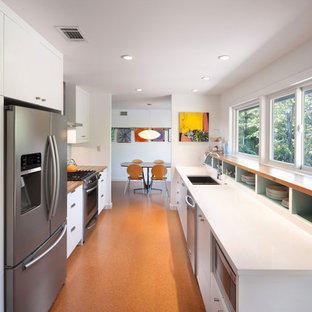 Design ideas for a small contemporary galley separate kitchen in Austin with a double-bowl sink, flat-panel cabinets, white cabinets, wood benchtops, blue splashback, ceramic splashback, stainless steel appliances, cork floors, no island, orange floor and white benchtop.