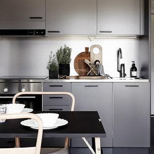 他の地域, のI型コンテンポラリースタイルのダイニングキッチンの写真 (ドロップインシンク、フラットパネル扉のキャビネット、グレーのキャビネット、ステンレスカウンター、シルバーの調理設備の、濃色無垢フローリング、アイランドなし)