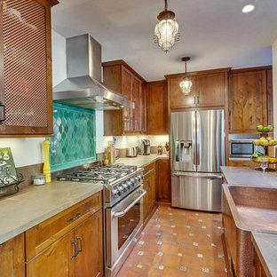 ロサンゼルスの中サイズのラスティックスタイルのおしゃれなキッチン (エプロンフロントシンク、落し込みパネル扉のキャビネット、茶色いキャビネット、珪岩カウンター、緑のキッチンパネル、セラミックタイルのキッチンパネル、シルバーの調理設備、テラコッタタイルの床、アイランドなし、赤い床) の写真