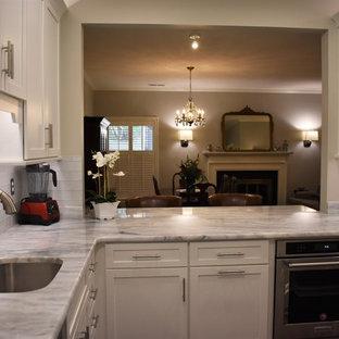 Klassische Wohnküche ohne Insel in L-Form mit Unterbauwaschbecken, Schrankfronten im Shaker-Stil, weißen Schränken, Quarzit-Arbeitsplatte, Küchenrückwand in Weiß, Rückwand aus Glasfliesen, Küchengeräten aus Edelstahl, Schieferboden, grünem Boden und grauer Arbeitsplatte in Sonstige