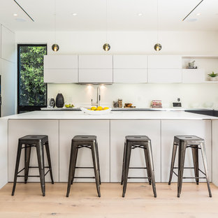 Contemporary kitchen designs - Kitchen - contemporary u-shaped light wood floor and beige floor kitchen idea in Los Angeles with flat-panel cabinets, white cabinets, an island and white countertops