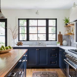Idéer för mellanstora lantliga brunt l-kök, med en undermonterad diskho, luckor med infälld panel, blå skåp, träbänkskiva, vitt stänkskydd, stänkskydd i marmor, rostfria vitvaror, mellanmörkt trägolv, en köksö och vitt golv