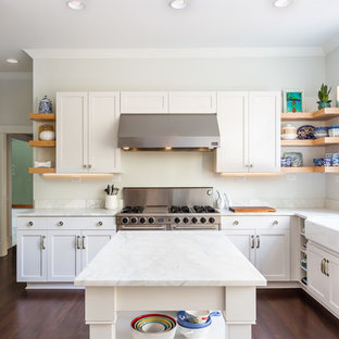 Large transitional kitchen photos - Example of a large transitional u-shaped dark wood floor and brown floor kitchen design in Raleigh with a farmhouse sink, shaker cabinets, white cabinets, stainless steel appliances, an island, marble countertops, white backsplash, marble backsplash and white countertops