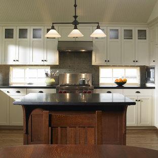 Стильный дизайн: угловая кухня в классическом стиле с техникой из нержавеющей стали, столешницей из гранита и фартуком из известняка - последний тренд