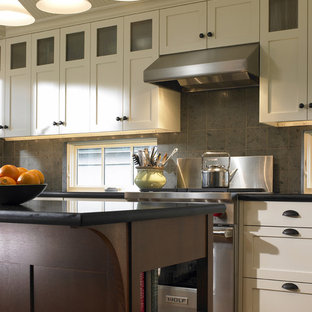 Elegant kitchen photo in Seattle with stainless steel appliances, shaker cabinets and gray backsplash