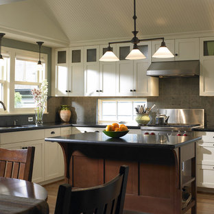 Cette photo montre une cuisine américaine chic avec un électroménager en acier inoxydable, un plan de travail en granite, un placard à porte shaker, des portes de placard blanches, une crédence grise et une crédence en pierre calcaire.