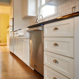 ポートランドの中くらいのおしゃれなキッチン (エプロンフロントシンク、シェーカースタイル扉のキャビネット、白いキャビネット、クオーツストーンカウンター、白いキッチンパネル、サブウェイタイルのキッチンパネル、シルバーの調理設備、リノリウムの床、アイランドなし) の写真