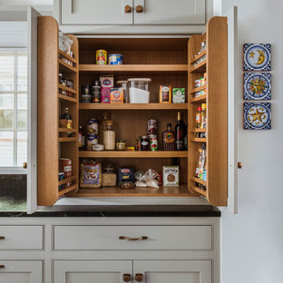Design ideas for a large classic u-shaped kitchen pantry in Portland with a submerged sink, beaded cabinets, grey cabinets, blue splashback, integrated appliances, an island, grey floors and black worktops.