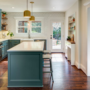Transitional kitchen remodeling - Inspiration for a transitional l-shaped medium tone wood floor and brown floor kitchen remodel in Portland with a farmhouse sink, recessed-panel cabinets, turquoise cabinets, white backsplash, subway tile backsplash, stainless steel appliances, an island and white countertops