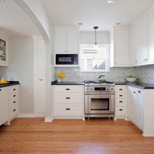 Large elegant u-shaped light wood floor eat-in kitchen photo in Seattle with white cabinets, gray backsplash, stainless steel appliances, a farmhouse sink, recessed-panel cabinets, granite countertops, glass tile backsplash and no island