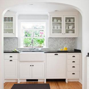 シアトルの広いトラディショナルスタイルのおしゃれなキッチン (エプロンフロントシンク、白いキャビネット、御影石カウンター、グレーのキッチンパネル、ガラスタイルのキッチンパネル、シルバーの調理設備、アイランドなし、ガラス扉のキャビネット、無垢フローリング) の写真