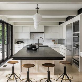 シアトルの中くらいのトランジショナルスタイルのおしゃれなキッチン (シングルシンク、シェーカースタイル扉のキャビネット、グレーのキャビネット、御影石カウンター、白いキッチンパネル、レンガのキッチンパネル、シルバーの調理設備、ライムストーンの床、ベージュの床、黒いキッチンカウンター) の写真