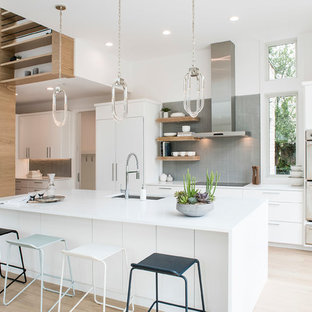 Photo of a mid-sized contemporary eat-in kitchen in Austin with an undermount sink, flat-panel cabinets, white cabinets, solid surface benchtops, grey splashback, glass tile splashback, stainless steel appliances, with island, white benchtop and light hardwood floors.