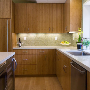 This is an example of a mid-sized midcentury u-shaped kitchen in San Francisco with an undermount sink, flat-panel cabinets, medium wood cabinets, stainless steel appliances, quartzite benchtops, beige splashback, glass tile splashback, light hardwood floors, with island, beige floor and white benchtop.