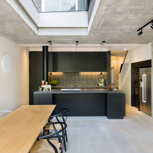 This is an example of a large industrial galley eat-in kitchen in London with an integrated sink, flat-panel cabinets, black cabinets, grey splashback, cement tile splashback, stainless steel appliances, light hardwood floors, with island, white floor and grey benchtop.