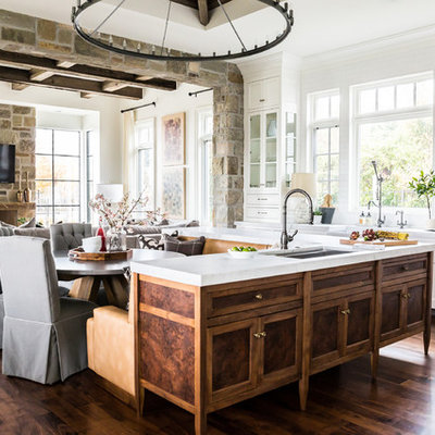 Inspiration for a large country dark wood floor eat-in kitchen remodel in Salt Lake City with a farmhouse sink, recessed-panel cabinets, medium tone wood cabinets, marble countertops, white backsplash, paneled appliances and an island