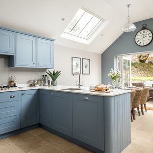 Large farmhouse l-shaped kitchen/diner in Gloucestershire with a single-bowl sink, blue cabinets, beige floors, beaded cabinets, grey splashback, glass sheet splashback, a breakfast bar and white worktops.