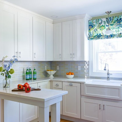 Inspiration for a small transitional u-shaped medium tone wood floor and brown floor kitchen remodel in Boston with a farmhouse sink, stainless steel appliances, white countertops, shaker cabinets, white cabinets, multicolored backsplash, subway tile backsplash and a peninsula
