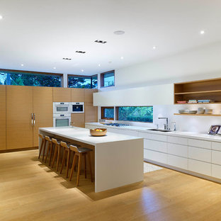 Design ideas for a large modern l-shaped open plan kitchen in Toronto with an undermount sink, flat-panel cabinets, white cabinets, solid surface benchtops, white splashback, white appliances, light hardwood floors and with island.