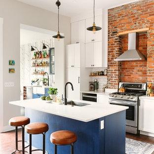 Mittelgroße Klassische Wohnküche in L-Form mit Unterbauwaschbecken, Schrankfronten im Shaker-Stil, blauen Schränken, Quarzwerkstein-Arbeitsplatte, Küchenrückwand in Weiß, Rückwand aus Metrofliesen, Küchengeräten aus Edelstahl, dunklem Holzboden, Kücheninsel, braunem Boden und weißer Arbeitsplatte in Sonstige