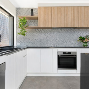 Design ideas for a contemporary l-shaped kitchen in Canberra - Queanbeyan with a drop-in sink, flat-panel cabinets, white cabinets, grey splashback, stainless steel appliances, with island, grey floor and grey benchtop.